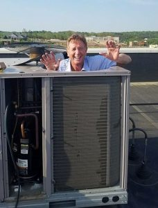 Picture of co-owner Dan McCarthy having fun fixing a rooftop central air unit.