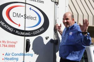 Smiling co-owner and HVAC expert Jim Workman waving next to the DM Select Services truck.